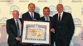 Festejo por el aniversario. Vignatti, Vila y Manzano, del Directorio de La Capital, y el senador Perotti (segundo desde la izquierda) posan junto al diploma enmarcado.