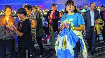 cerca del crimen. Una mujer sostiene una bandera argentina.