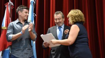 Carola Nin entrega la distinción y al presidente del directorio Daniel Vila y su hijo Agustín Vila.