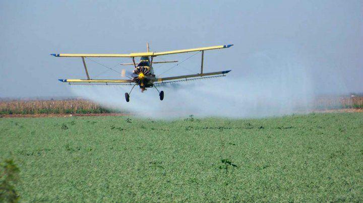 Una avioneta fumiga la cosecha en una zona rural.
