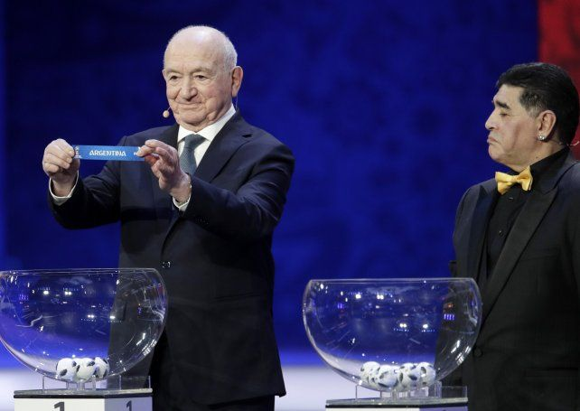 El exfutbolista rusoNikita Simonyan exhibe el papel con el nombre de Argentina ante la mirada de Diego Maradona.