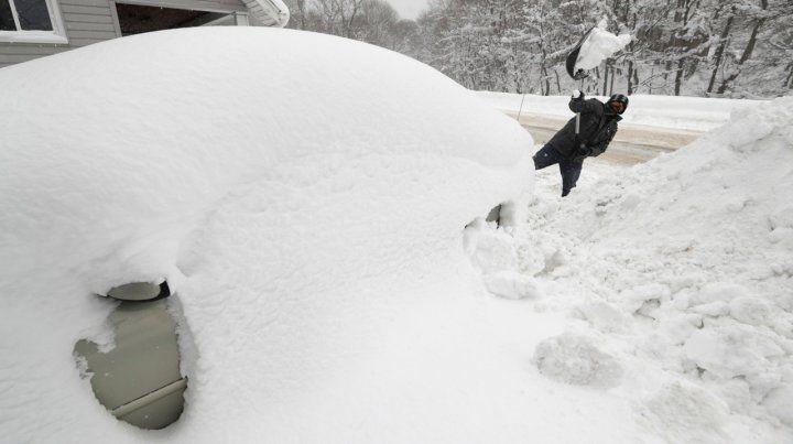 Un hombre intenta desenterrar su auto de la montaña de nieve en Erie