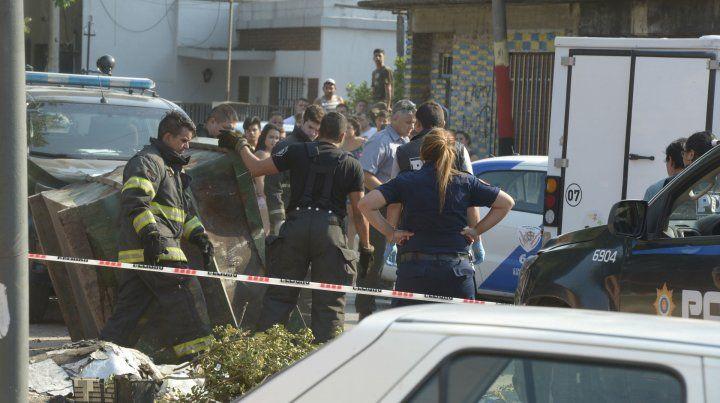 La policía trabaja junto al volquete donde apareció el cuerpo de la víctima