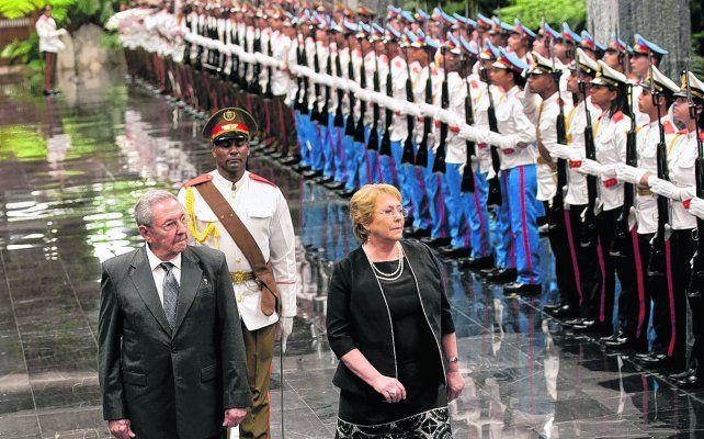 aliados. Raúl Castro acompaña a Bachelet en el tradicional saludo a la guardia militar