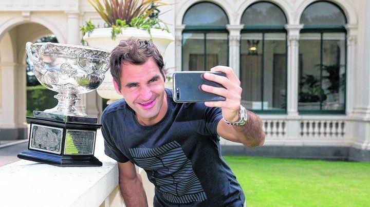 Alta selfie. Federer posa con el trofeo Norman Brookes con la casa de gobierno de Melbourne de fondo.El suizo ganó por sexta vez el abierto de tenis de Australia a los 36 años.