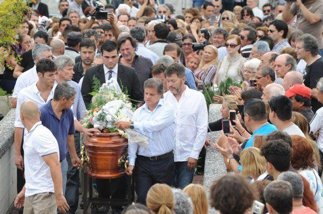 El periodista Enrique Sacco, pareja de Débora Pérez Volpin, y Marcelo Funes, ex marido (de barba), portando el féretro.