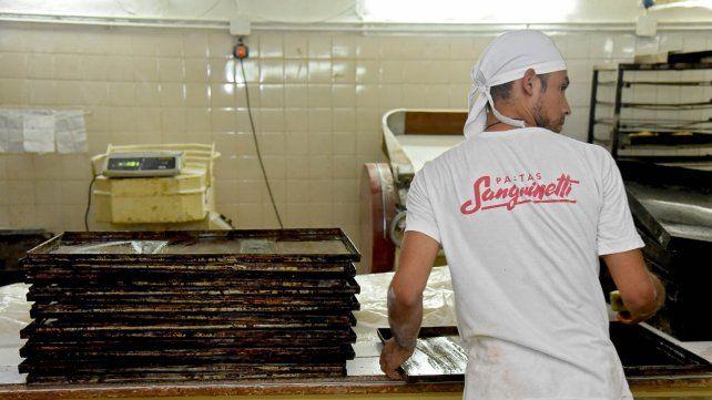 En acción. Uno de los jóvenes que se insertó en el mundo laboral prepara pastas dentro de una fábrica rosarina que apostó al proyecto estatal.