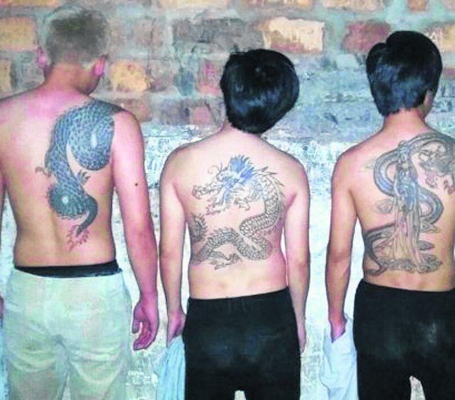 condenados. Los tres orientales tienen tatuadas sus espaldas.