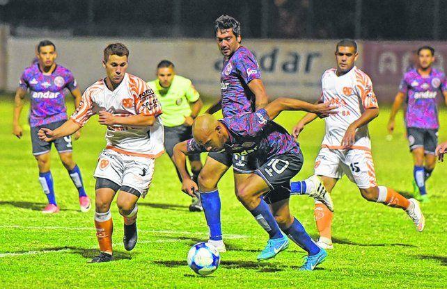 Mirando la redonda. Diego Migueles se lleva la pelota mientras Sacino se acerca con intenciones de cortar el avance.