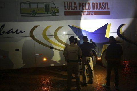 Intolerancia. Policías inspeccionan uno de los colectivos baleados de la caravana proselitista de Lula.