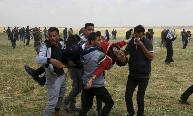 Caído. Los palestinos retiran a un herido grave de la zona.