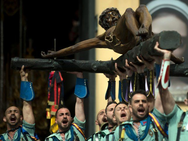 Legionarios alzan el Cristo de la Buena Muerte en Málaga.
