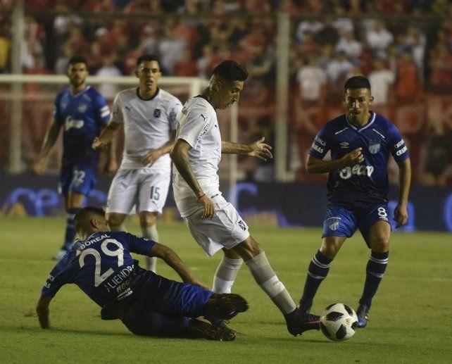 Tucumanos. Aliendro marca abajo y el goleador Guillermo Acosta (8) mira de frente.