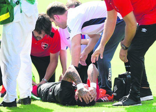 Dolor intenso. Sarmiento se toma la cabeza tras la lesión mientras el médico Bóttoli lo atiende dentro del campo de juego.