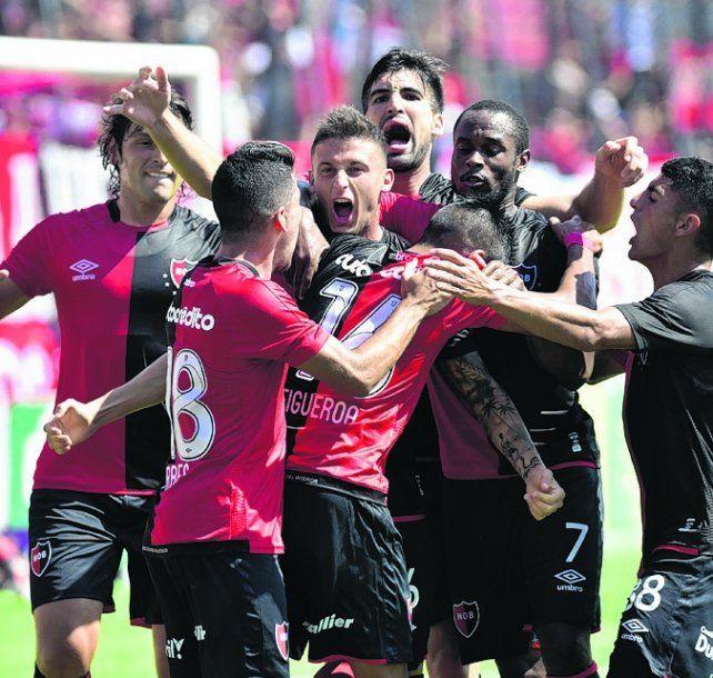 Apertura. Héctor Fértoli grita su gol contra Tigre rodeado por los compañeros.