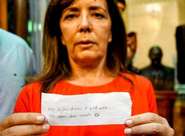 La diputada nacional Gabriela Cerruti exhibe el papel que le arrojó el ministro Luis Caputo.