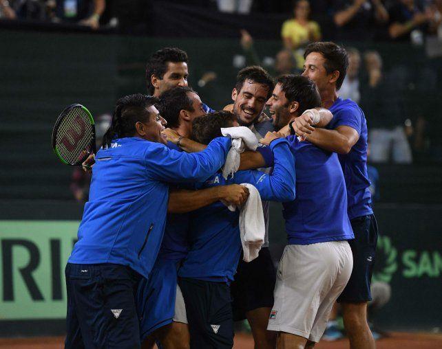 Guido Pella logró el quinto punto de la serie y sus compañeros del equipo argentino se abrazan en el festejo.