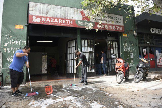 Dar una mano. Dos jóvenes limpiaban ayer la vereda del taller.