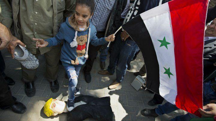 Una niña pisa un muñeco de Trump en una de las manifestaciones de este sábado tras los ataques.