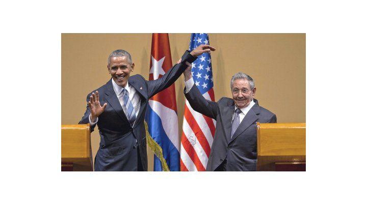 Apretón de manos. Castro levanta el brazo de Obama en el Palacio de la Revolución
