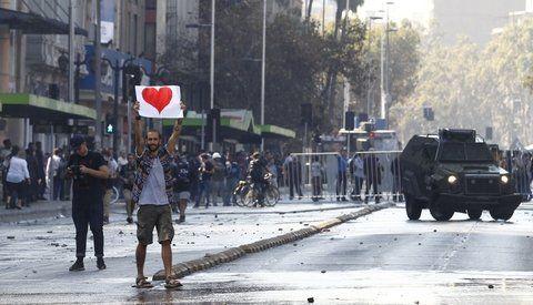 Un joven sostiene un cartel con un corazón durante los incidentes que se  produjeron en la marcha de estudiantes en Santiago.