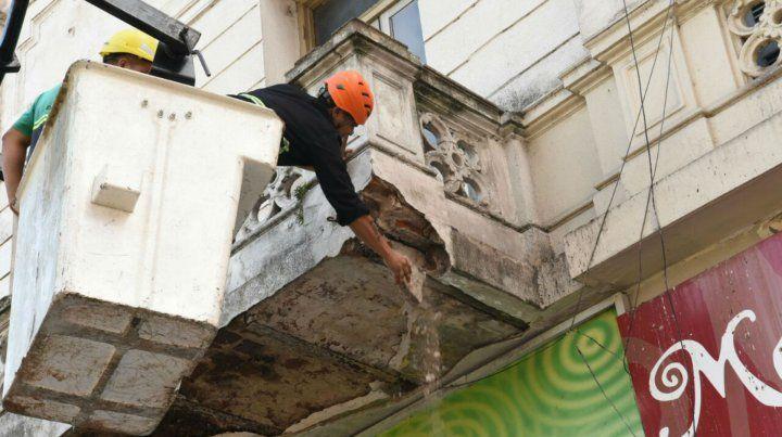 Personal de Defensa Civil y Central de Emergencias trabajan sobre el balcón sobre calle San Luis.