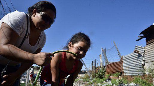 Poca agua. En barrio Alvear, Yanina le presta su manguera a otros vecinos para que puedan abastecerse.