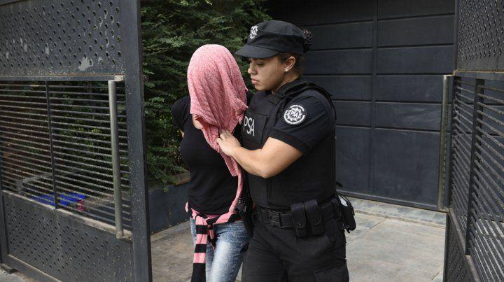 Una de las detenidas sale con la cara cubierta de uno de los allanamientos.