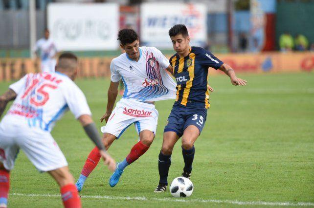 Joaquín Pereyra toma de la camiseta a un rival.