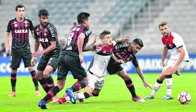 Fue una lucha. Fertoli intenta eludir a Lucho González. En Curitiba fue todo de Paranaense.