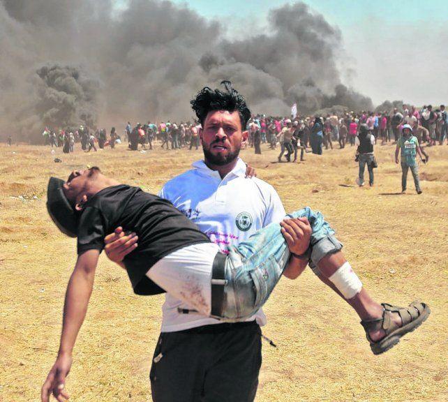 Sin vida. Un palestino retira el cuerpo de un caído en la zona de la frontera.