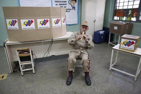 solo y aburrido. Un miembro de la Milicia Bolivariana toca una flauta en una desierta mesa de Caracas.