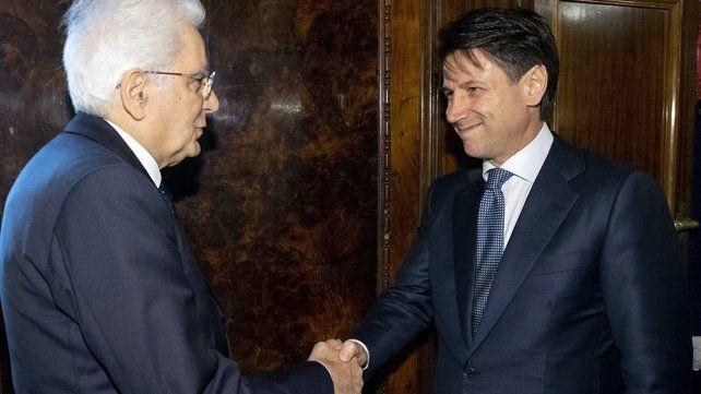 Con reservas. Mattarella (izquierda) estrecha la mano del futuro premier italiano al recibirlo en el Palacio Quirinale.