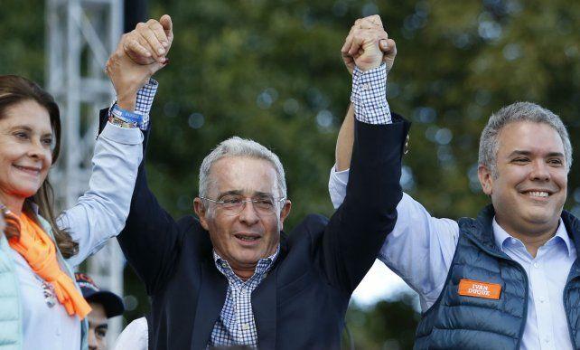 Alvaro Uribe (centro) alza los brazos de Iván Duque y de su compañera de fórmula en la campaña.