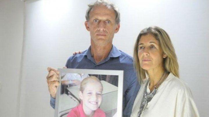 Los padres de Justina muestran la foto de su hija.