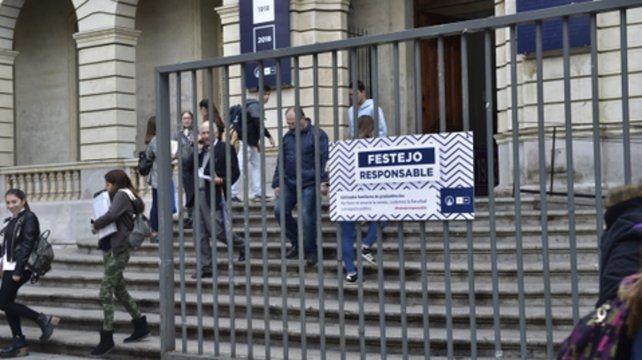 Responsabilidad. Un cartel invita a festejar sin ensuciar en la puerta de la Facultad de Derecho de la UNR.