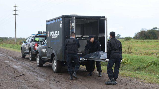 El final. El hombre asesinado en un camino de tierra es cargado en la mortera policial.