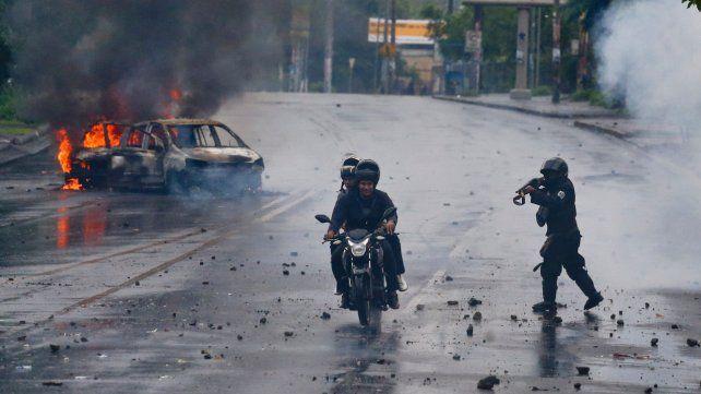 Tensión social. Un policía apunta su arma hacia los ocupantes de una motocicleta durante una protesta.