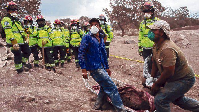 Pobladores intentan reconocer un cuerpo en el pueblo de El Rodeo. Las cenizas taparon todo.