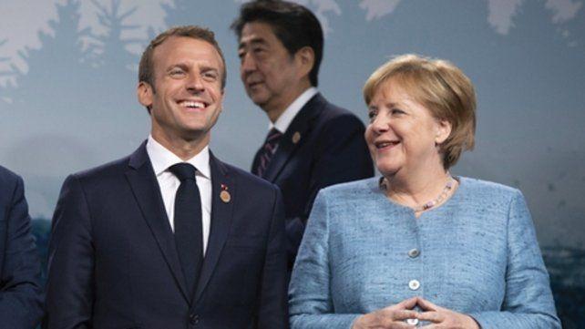Sonrisas. Macron y Merkel en la foto de grupo. Atrás