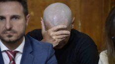 Oculto. El policía acusado por el fiscal se tapa la cara durante el juicio.