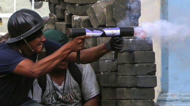 Choques. Un manifestante antigubernamental dispara un mortero casero.