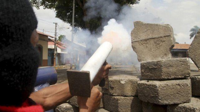 Tensión social. Un manifestante lanza un mortero casero hacia las fuerzas de choque sandinistas.