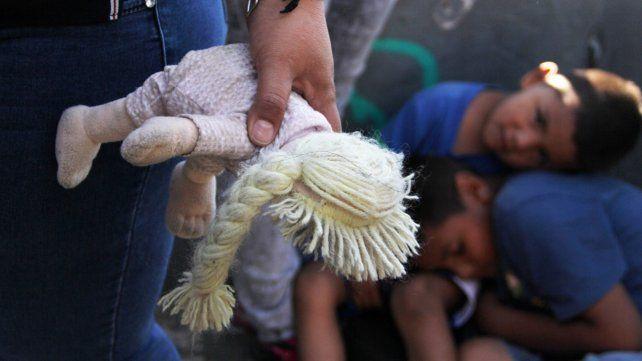 Larga espera. Menores demorados junto a su mamá en uno de los pasos fronterizos entre EEUU y México.