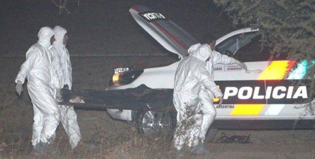 Los peritos forenses retiran el cuerpo de la joven asesinada.