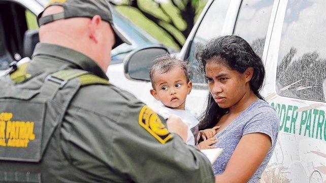 Una Inmigrante hondureña y su niña es detenida por la policía migratoria después de cruzar ilegalmente la frontera.