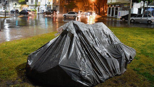 Bajo la lluvia. Algunos se guarecen como pueden.