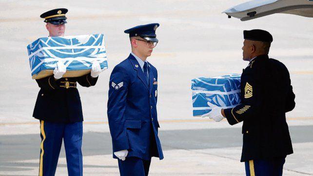 Honores. El traslado de cajas con los restos cubiertas con la bandera de ONU.