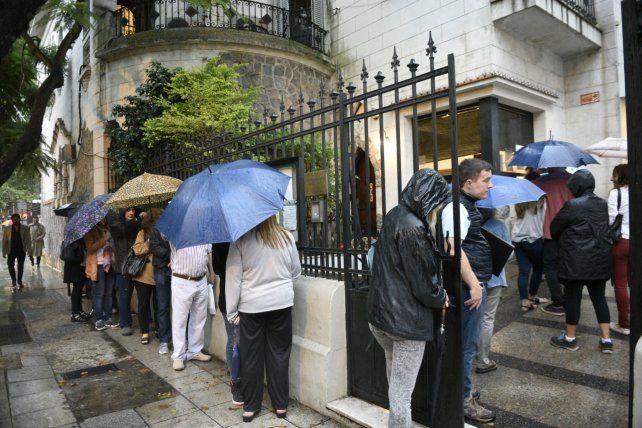 Bajo la lluvia. El público espera ingresar al Consulado de Italia para realizar gestiones sobre ciudadanía.