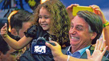 El diputado Bolsonaro enseña a una pequeña a hacer la mímica del uso de un revólver.